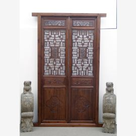 The Chinese door made of dark hardwood with elaborate details
